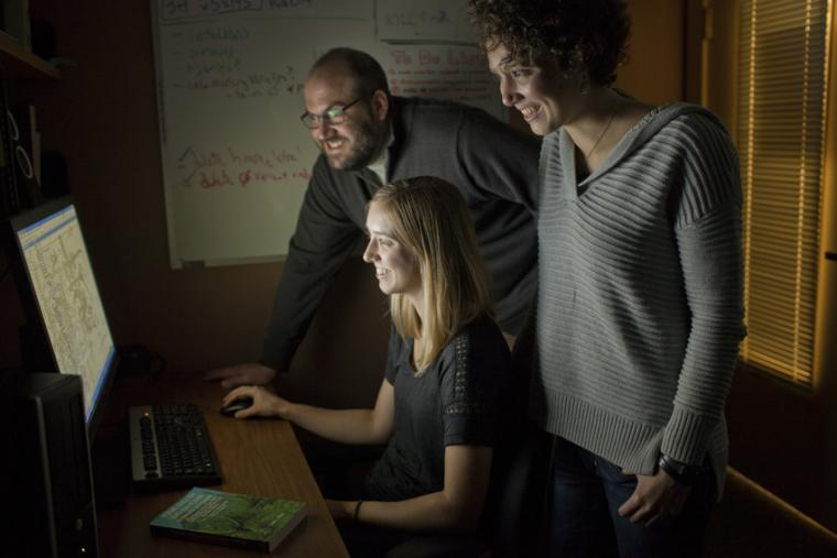 Three people looking at a computer screen.