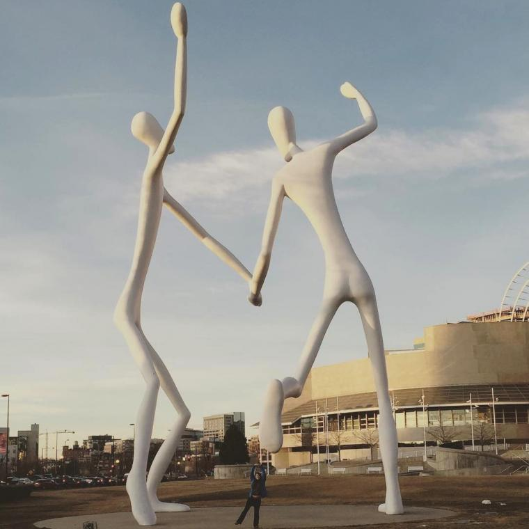Person posing beneath a large statue of two people