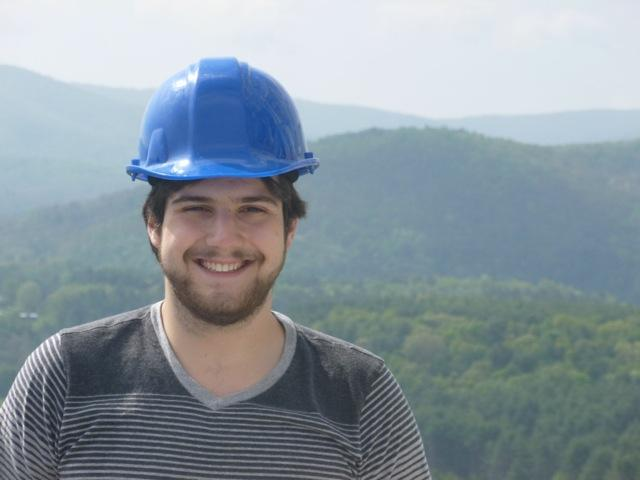 A person in a hard hat poses for a photo in front of rolling hills