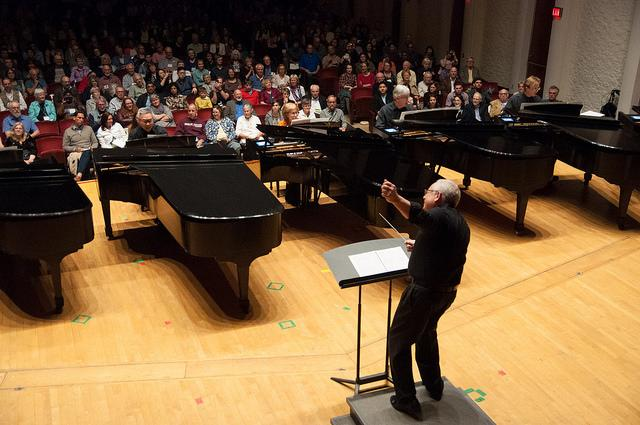 Photograph of a conductor directing piano players.
