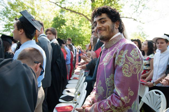 Photo of a man in formalwear amongst a standing audience of graduating students
