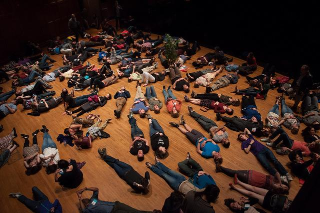 Photograph of many people lying down on a floor.