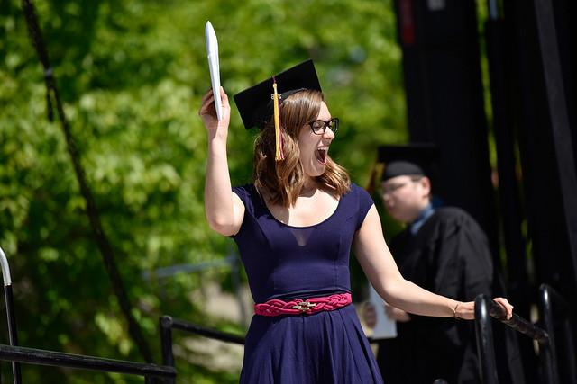 Photo of a student wearing a graduation cap and holding a diploma aloft