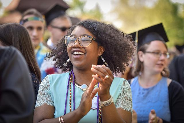 Photo of a graduating student clapping