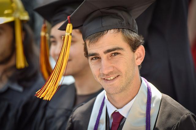 Photo of a man clothed in commencement regalia