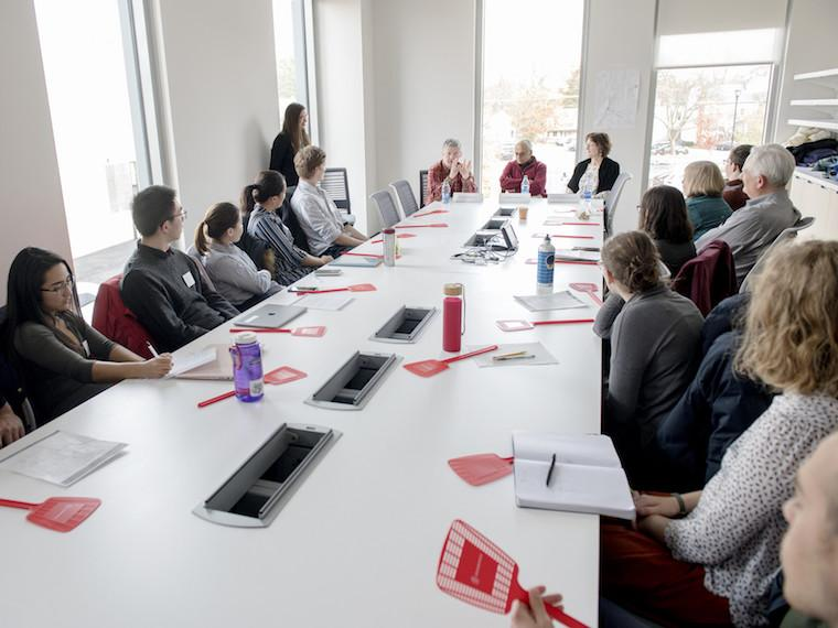Students sit at a long conference room table.