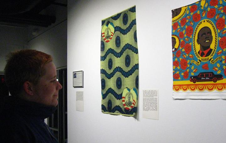 Photograph of someone looking at fabric that is hung from the wall.