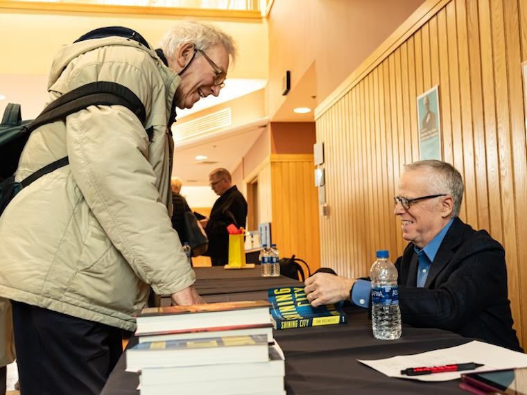A man signs a book at a book signing for another man standing in front of him.