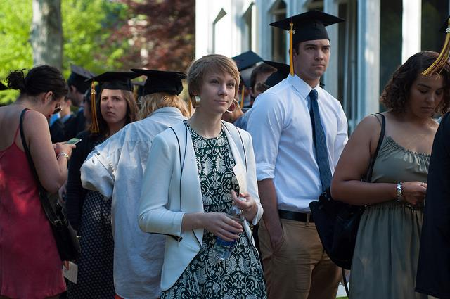 Photo of a group of people in commencement regalia and formalwear