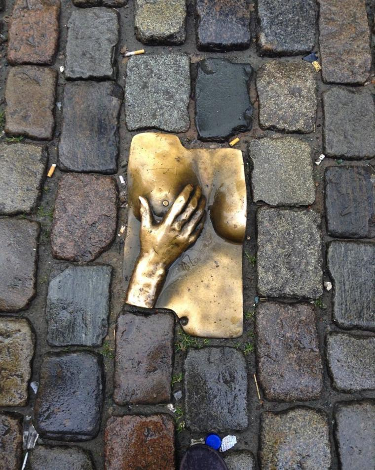 Photo of a tile in a cobblestone path depicting a hand touching a breast