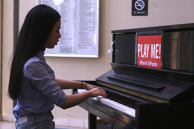 Photograph of woman playing the piano.