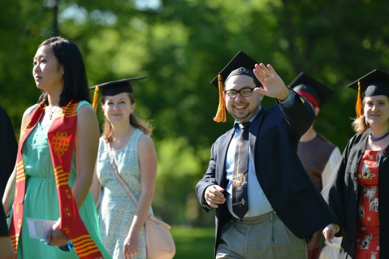 A man in formalwear and a commencement cap smiles and waves as he walks past with others who are similarly dressed