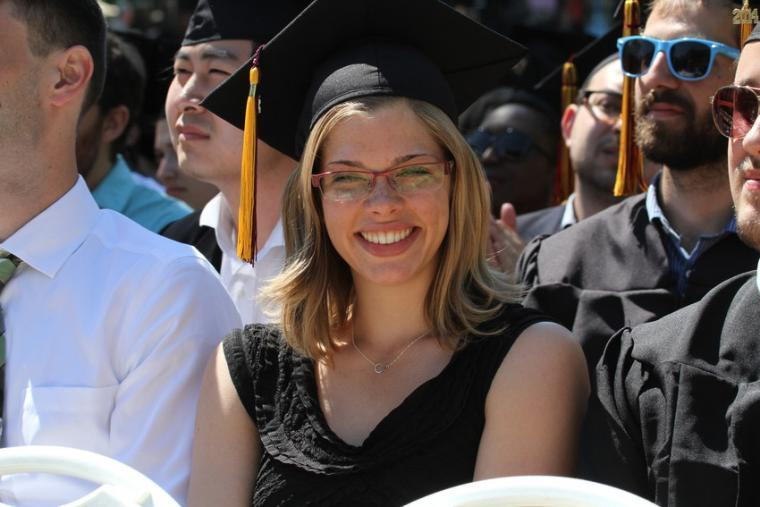 A woman wearing a commencement cap smiles from amongst a crowd