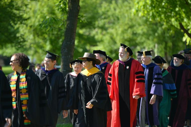 A group of people in commencement regalia walking outdoors