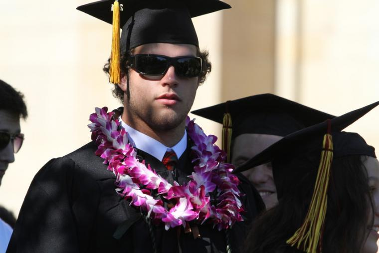 A man dressed in commencement regalia and sunglasses, with a couple of leis around his neck