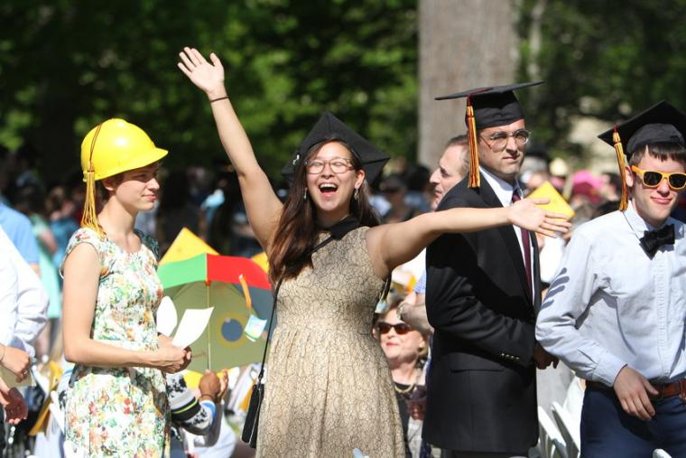 A woman with a commencement cap raises her arms in celebration as three others look on