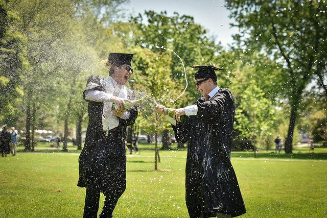 Two graduates open champagne on a field