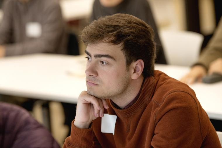 A student looks intently at a speaker in a classroom.