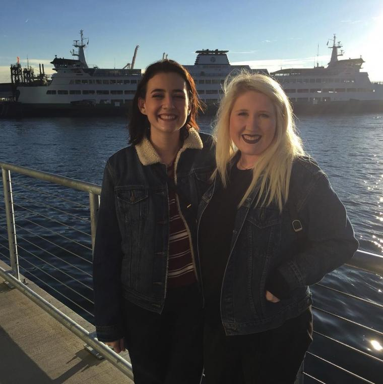 Two women stand by the water with a large ship in the background
