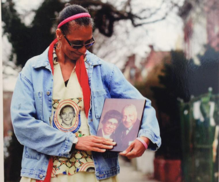 Photograph of a woman holding a picture of a man and a woman.