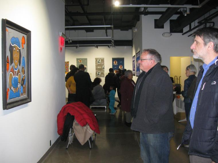 Photograph of two men looking at a painting on the wall and there are several people in the background.