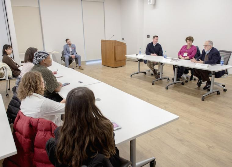 Students listen to three panelists in front of a room.