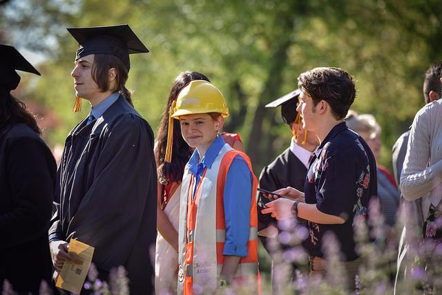 A person dressed in a hard hat a visibility vest in line with others in commencement regalia