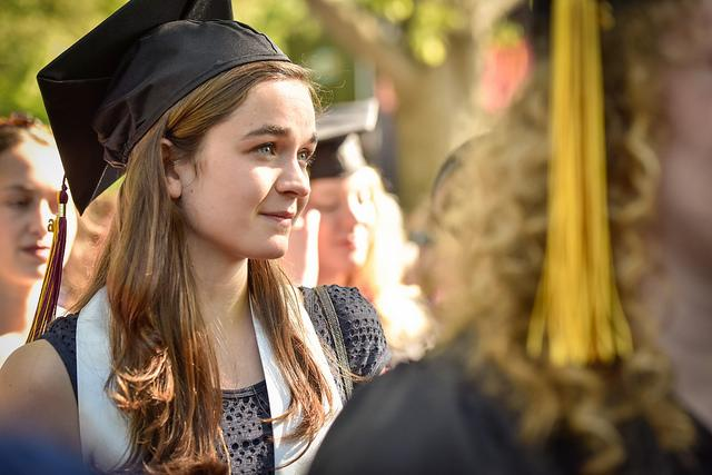 Photo of a woman wearing a graduation cap amongst a crowd of graduates
