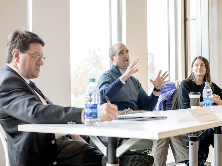 A panel of three professionals sit in front of a classroom.