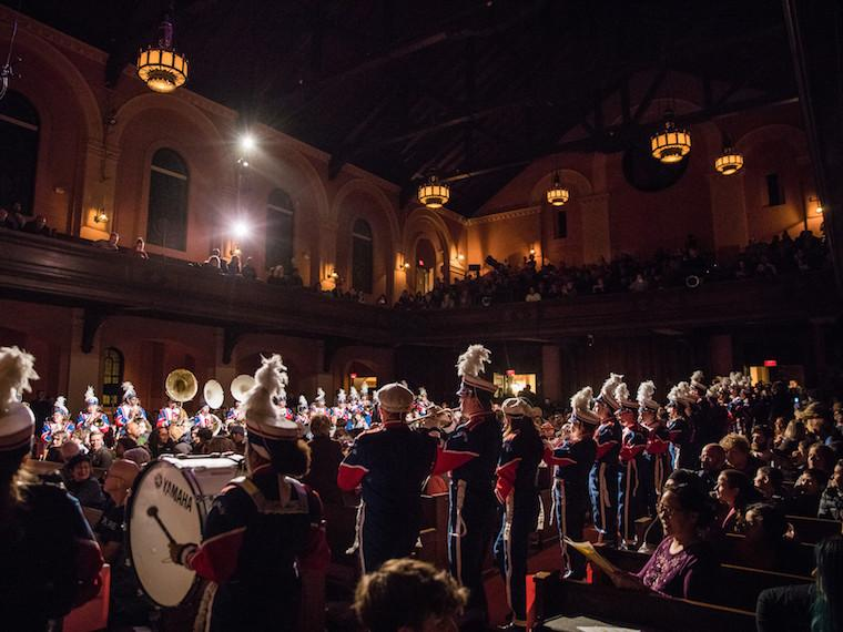 Marching band performs in the isles of Finney Chapel.