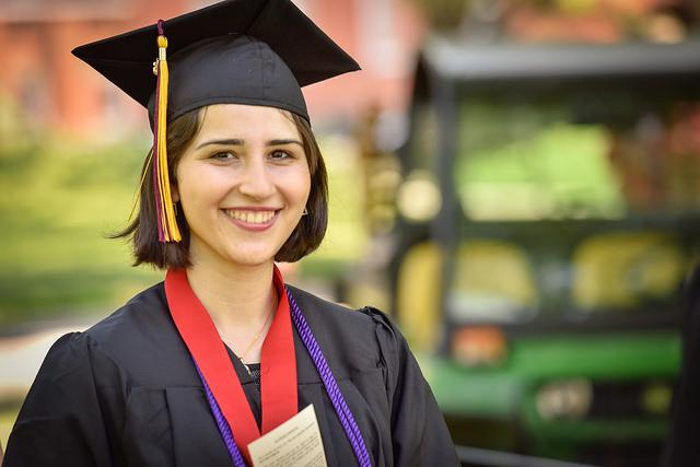 Photo of a woman dressed in commencement regalia