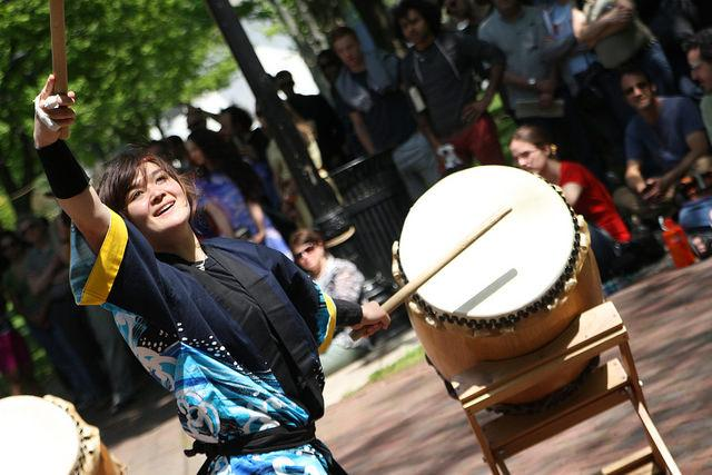 A female drum performer and people in the background.