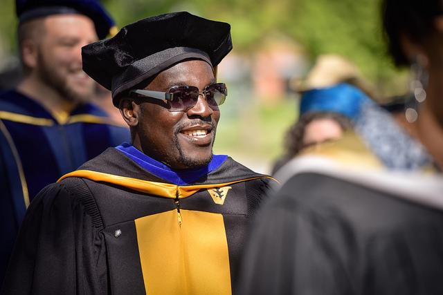 Photo of a man dressed in commencement regalia