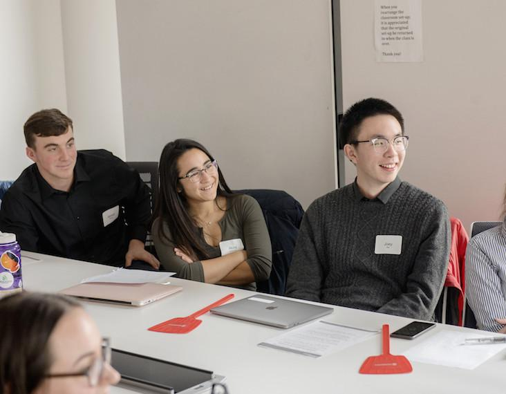 Three students in a conference room look toward the front of the room
