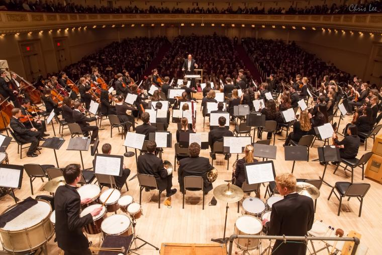 Photograph of the full orchestra and the man conducting.