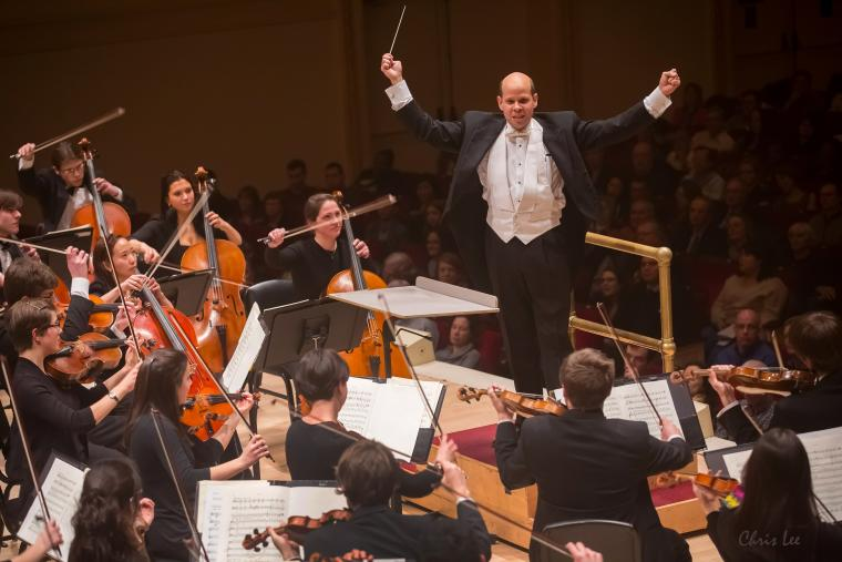 A man conducts of the Oberlin College orchestra at Carnegie Hall.