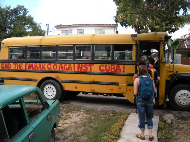"A schoolbus with the phrase ""End the embargo against Cuba"" painted on the side"
