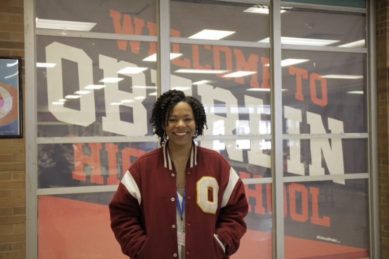 "A person poses in front of a banner that reads ""Welcome to Oberlin High School"""