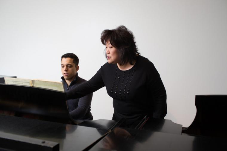 A professor instructs a student at side-by-side pianos