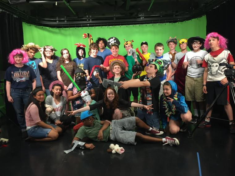 A large group of young people pose for a photo in front of a green screen