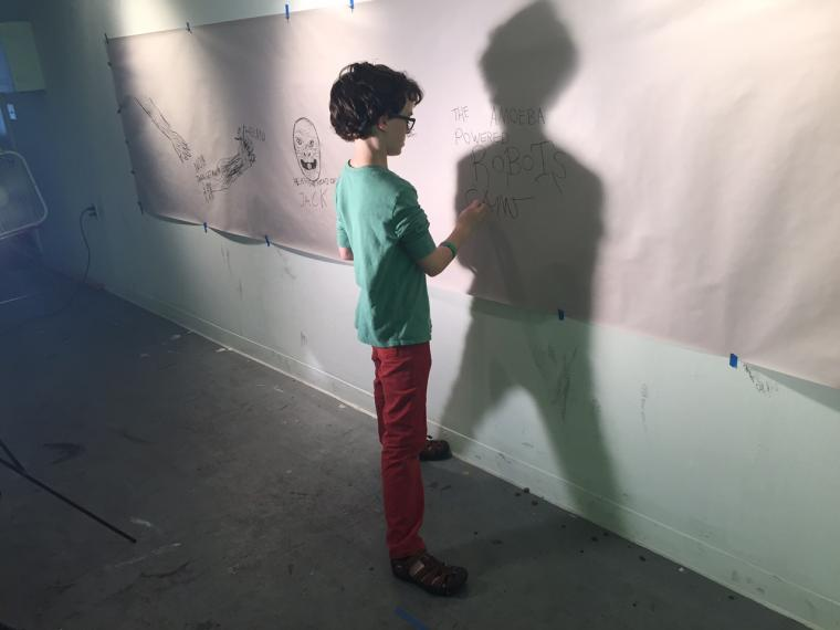 A boy writes on a large piece of paper taped to a wall