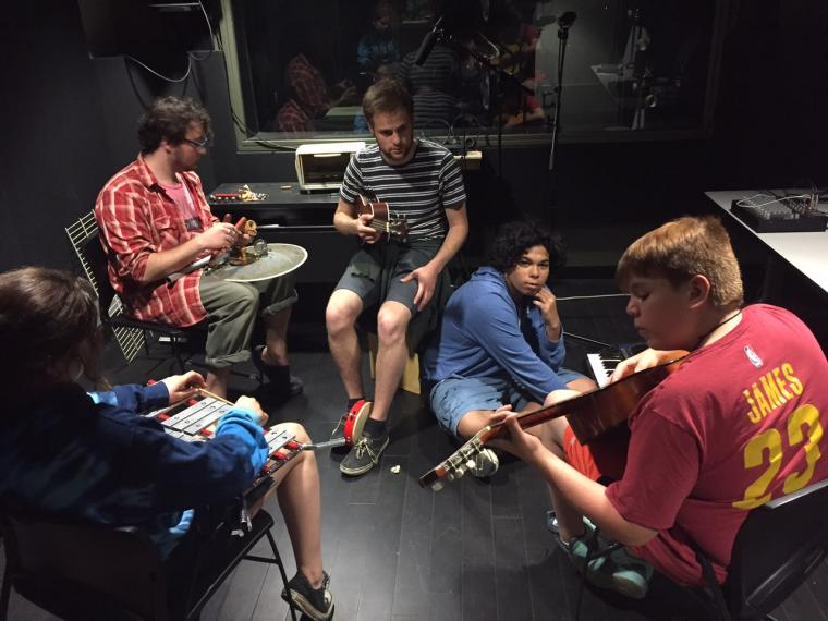 Five people lounge around a recording studio with instruments