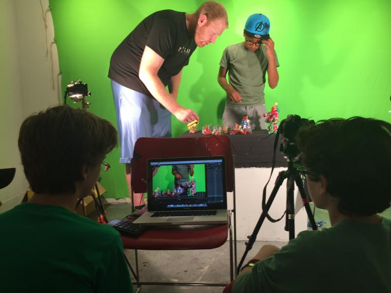 A man and a boy arrange figures on a table in front of a green screen while two others film
