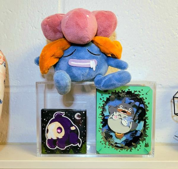 """A display case filled with a paper theater of Studio Ghibli's """"My Neighbor Totoro"""" and a 2x2 painting of a Pokémon, Duskull. On top of the display case sits a stuffed plush of another Pokémon, Gloom."""
