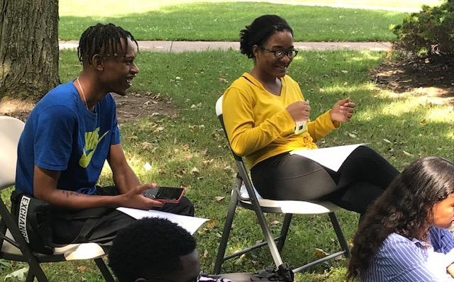 Two students sitting on chairs outside