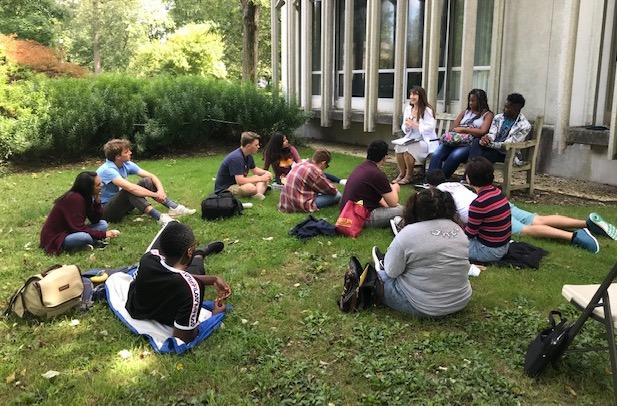 Twelve students sitting on lawn facing a staff member with a building on the right