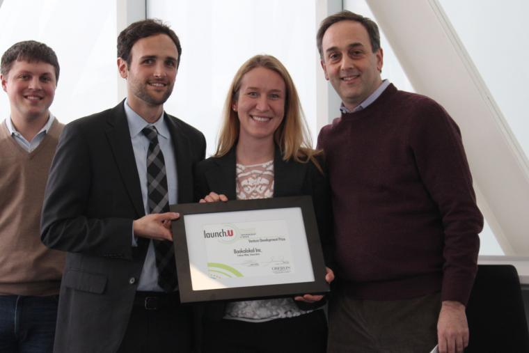 Photograph of four people: Three men and one woman who is holding an award.