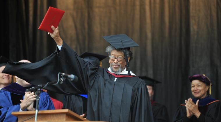 A man in commencement regalia holds up a red rectangle