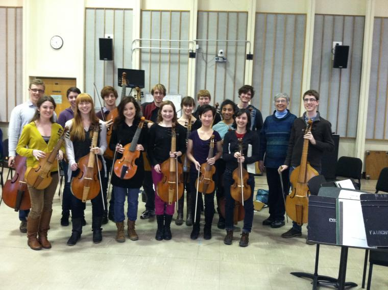 Photograph of men and women holding various string instruments.