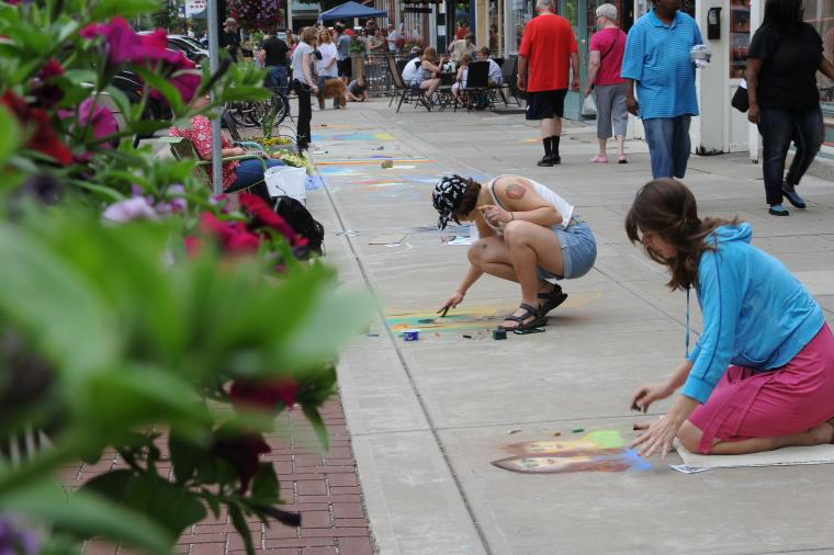 Two people draw with chalk on a busy sidewalk